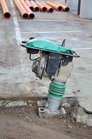 pic of vibration plate  - Vibratory plate compactor compacting sand at road construction site - JPG
