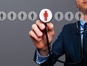 image of recruitment  - Businessman hand with stethoscope - JPG