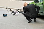 stock photo of accident victim  - Sad Male Driver After Collision With Bicycle On Road - JPG