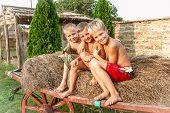 stock photo of hay bale  - boys sitting on a hay bale - JPG