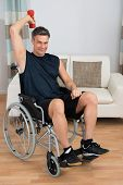 image of handicapped  - Handicapped Man On Wheelchair Working Out With Dumbbell At Home - JPG