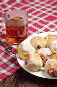 stock photo of baked raisin cookies  - Cookies with raisins in plate and tea cup on table covert red tablecloth - JPG