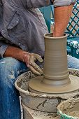 foto of molding clay  - Young artist shaping a clay pot with hands - JPG