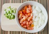 foto of onion  - Cuisine and Food Chopped Tomatoes Onions and Spring Onions on A Wooden Cutting Board - JPG