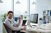 stock photo of indian  - Portrait of happy Indian entrepreneur in his office - JPG