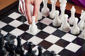 foto of chessboard  - Hand with white pawn on chessboard closeup - JPG