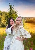 picture of national costume  - Two ukrainian girls in national costumes at the evening flower meadow