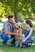 image of dog park  - Father and daughter with their pet dog in the park on a sunny day - JPG