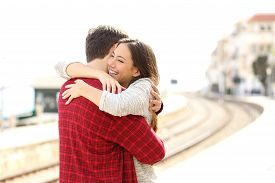 stock photo of hug  - Happy couple hugging in a train station after arrival - JPG
