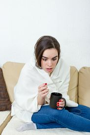 pic of high fever  - Upset woman with thermometer sick colds flu fever and migraine in bed with cup of tea or coffee - JPG