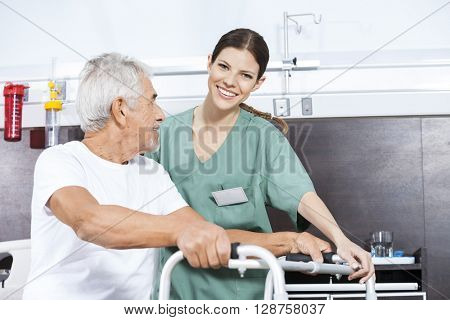 Nurse Assisting Senior Man To Use Walker At Rehab Center