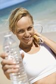 Caucasian young adult woman holding jump rope and water bottle on beach.