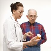 Mid-adult Caucasian female doctor pointing at prescription bottle as elderly Caucasian male looks at