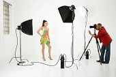 Young adult female Caucasian model being photographed in studio by young adult African American male