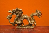 Chinese Taoist wisdom brass dragon statue against orange wall.
