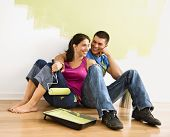 Couple sitting on floor smiling in front of partially painted wall in home.
