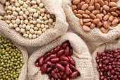 Assortment Of Beans And Lentils In Hemp Sack On Wooden Background. Green Bean, Groundnut, Soybean, R poster