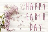Happy Earth Day Text Sign On Beautiful Lilac  Flowers On Rustic White Wooden Background Top View. Gr poster