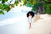 Young Biracial Asian Caucasian Woman Or Teen Walking On Beach Holding Umbrella On Overcast Rainy Day poster