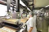 Production Of Pralines In A Factory For The Food Industry - Conveyor Belt Worker With Chocolate poster
