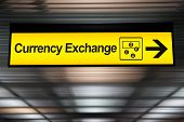 Постер, плакат: Sign Currency Exchange At The Airport With Money Currency Icon And Arrow For Direction To Currency E