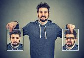 Young Cheerful Hipster Holding Photos With Different Emotions Having Problems With Mood Change. poster