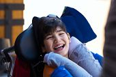 Biracial Asian Caucasian Disabled Boy In Wheelchair Smiling Outdoors. He Has Cerebral Palsy. poster