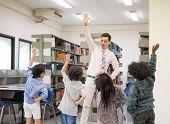 Happy Children And Teacher In Learning Class At Library. Boy Raised Hand Up His Hand To Answer A Que poster