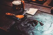 Closeup of putty knife on table with oil paint poster