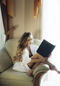 Lady With Busy Face In Bathrobe Reads Book Near Window. Girl Enjoys Morning Reading Siting On Armcha poster