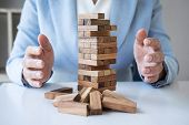 Alternative Risk And Strategy In Business, Business Womans Hands Protect Balance Wooden Stack With  poster