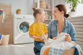 Beautiful young woman and child girl little helper are having fun and smiling while doing laundry at poster