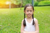 Portrait Of Beautiful Little Asian Child Girl With Two Ponytail Hair In The Garden With Morning Sunl poster