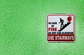 Red, Black And White Caution Sign With Person Running From Fire By Stairs And Warning Not To Use Ele poster