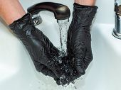Stylist Washing Hands In Washstand, Close Up View. Stylists Hands In Black Rubber Gloves. Photograph poster