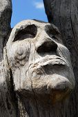 stock photo of totem pole  - A close up photo of a wood carved mans face with weathered surface - JPG