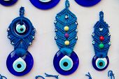 Blue Turkish evil eye with handcraft hanging at the wall
