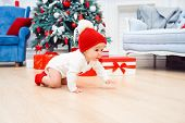 Adorable Smiling Infant Crawling On The Parquet To The Christmas Gifts Near His Mom Which Sits On Th poster