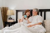 Asian Senior Couple Talking On Bed At Home. Asian Senior Chinese Grandparents, Husband And Wife Happ poster