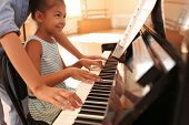 Young Woman Teaching Little Girl To Play Piano Indoors poster