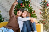 Young asian adult teenager couple take selfie photographing for celebrateing christmas holiday toget poster