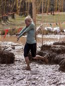 POCONO MANOR, PA - APR 28: A woman runs through an obstacle with electrified wires at Tough Mudder o