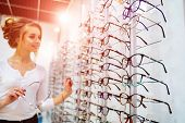 Row Of Glasses At An Opticians. Eyeglasses Shop. Stand With Glasses In The Store Of Optics. Woman Ch poster