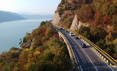 Cars Crossing A Bridge Over The Danube. On One Side Is The Danube And On The Other Side Trees With R poster