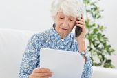 Elderly woman reading papers on the phone in the living room