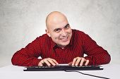 image of pervert  - Bald yopung adult man sitting at the table with keyboard in front of the computer - JPG