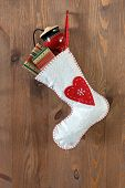 White Christmas stocking filled with traditional gifts and toys hanging by a rusty nail in an old do