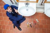 Cheerful plumber repairing sink showing thumb up in public bathroom