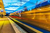 stock photo of commutator  - Railroad travel and transportation industry business concept: summer evening view of high speed commuter passenger train departing from railway station platform with motion blur effect