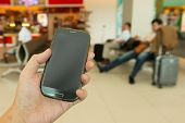 stock photo of handphone  - Close up of hand holding smartphone at airport - JPG
